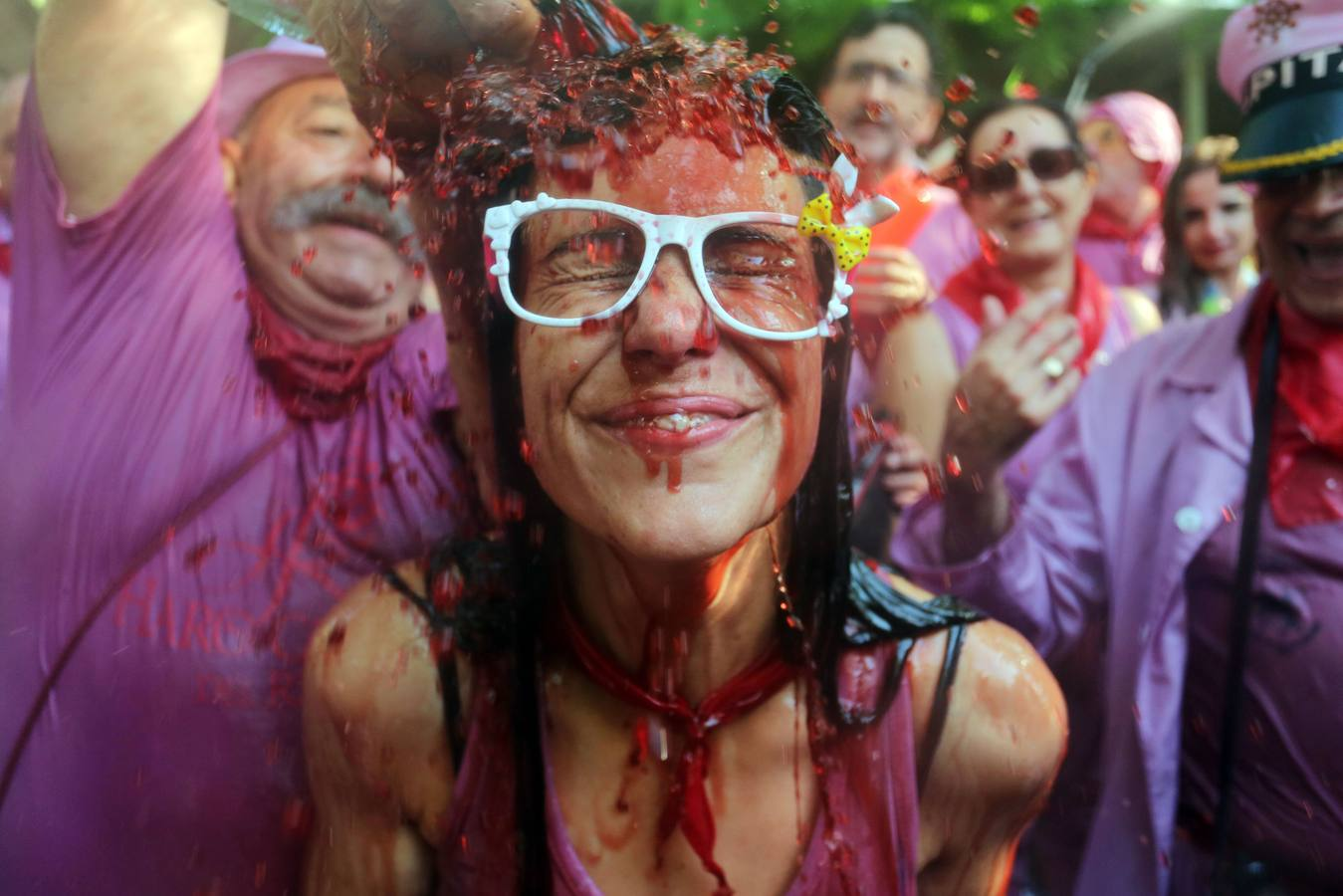 "TOPSHOTS A man pours red wine on a girl's head during the""Batalla del Vino"" (Battle of Wine) in Haro, on June 29, 2015. Every year thousands of locals and tourists climb a mountain in the northern Spanish province of La Rioja to celebrate St. Peter's day covering each other in red wine while tanker trucks filled with wine distribute the alcoholic beverage to water pistols, back mounted spraying devices, buckets which are randomly poured on heads and into any other available container. More than nine thousand people threw around 130,000 litres of wine during this year's Haro Wine Festival, according to local media. AFP PHOTO / CESAR MANSO"